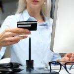 kobieta płaci kartą przed komputerem