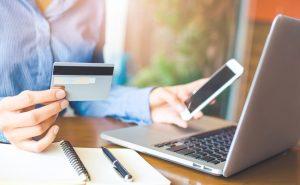 kobieta przy laptopie z kartą płatniczą w ręce