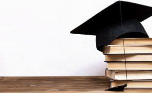 Powstał nowy kierunek studiów. Nowoczesne technologie w finansach – Fintech. Czapka studencka i książki